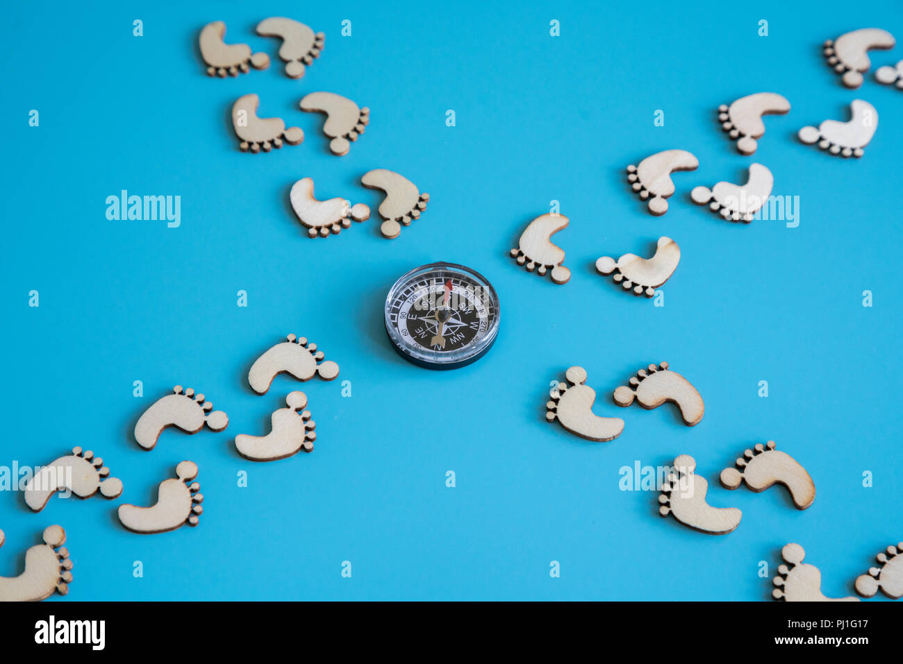 The concept of choosing the right way. Footprints on a blue background and a compass. - Stock Image