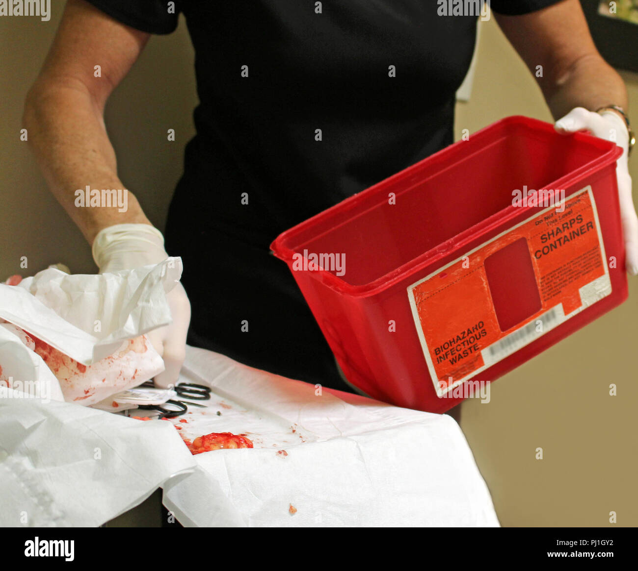 Cleaning up medical waste after a surgery - Stock Image
