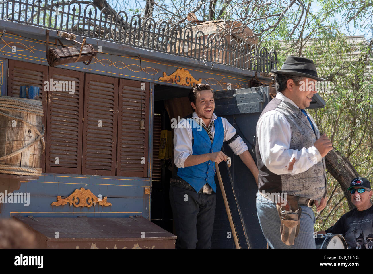 Western style dressed actors on stage with medicine wagon, one holding a cane. - Stock Image