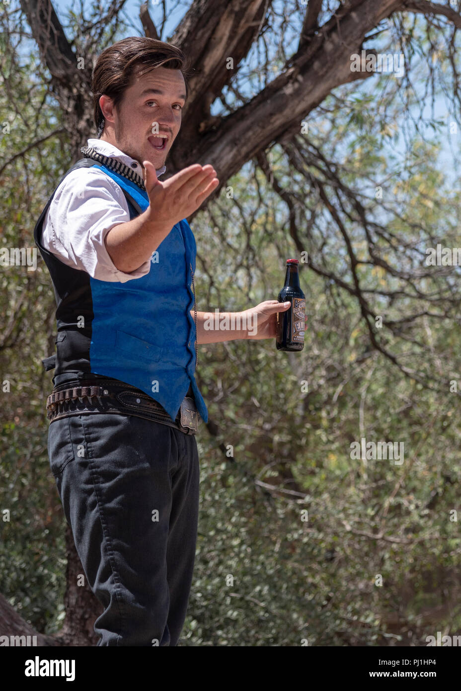 Actor dressed in old West style clothes describes the Benifits of the bottle of elixir in his had. - Stock Image