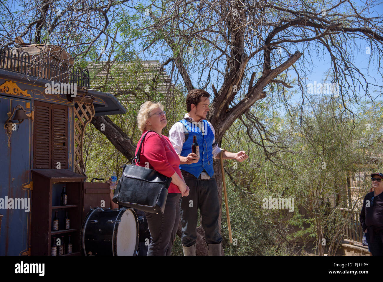 Tourists volunteers with actor in old west medicine show. Actor is holding a bottle of elixir. - Stock Image