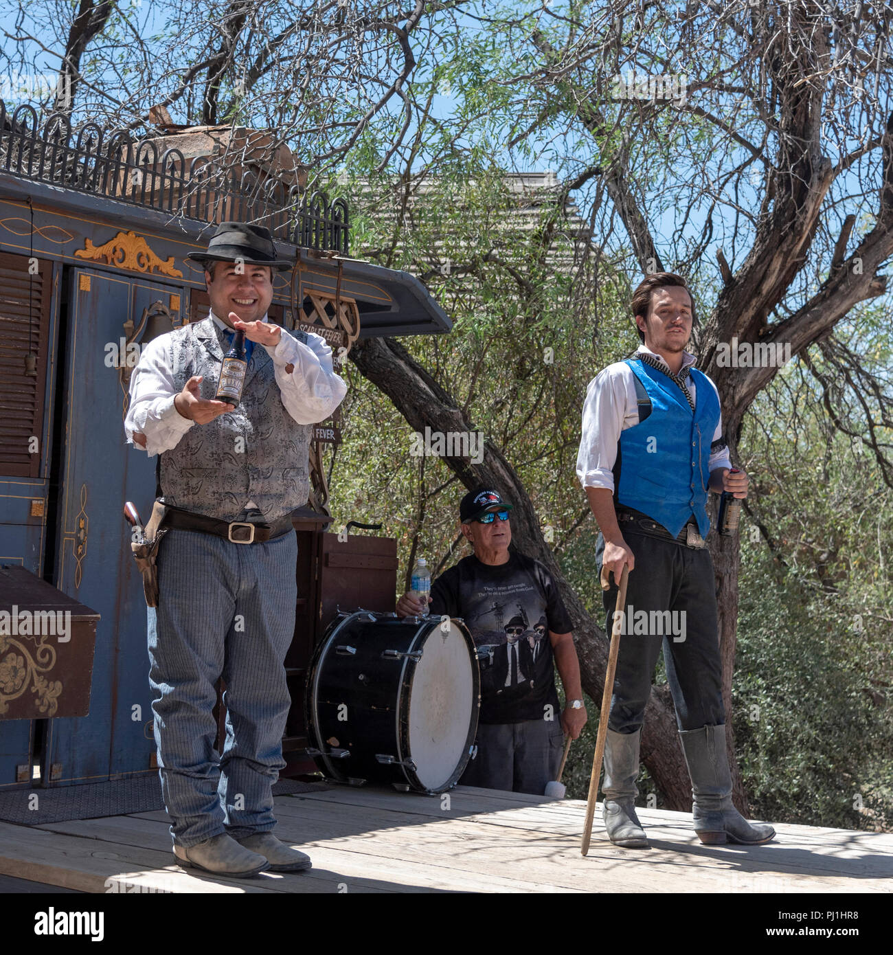 Western actors in medicine show holding bottles of elixir and tourists in background. - Stock Image