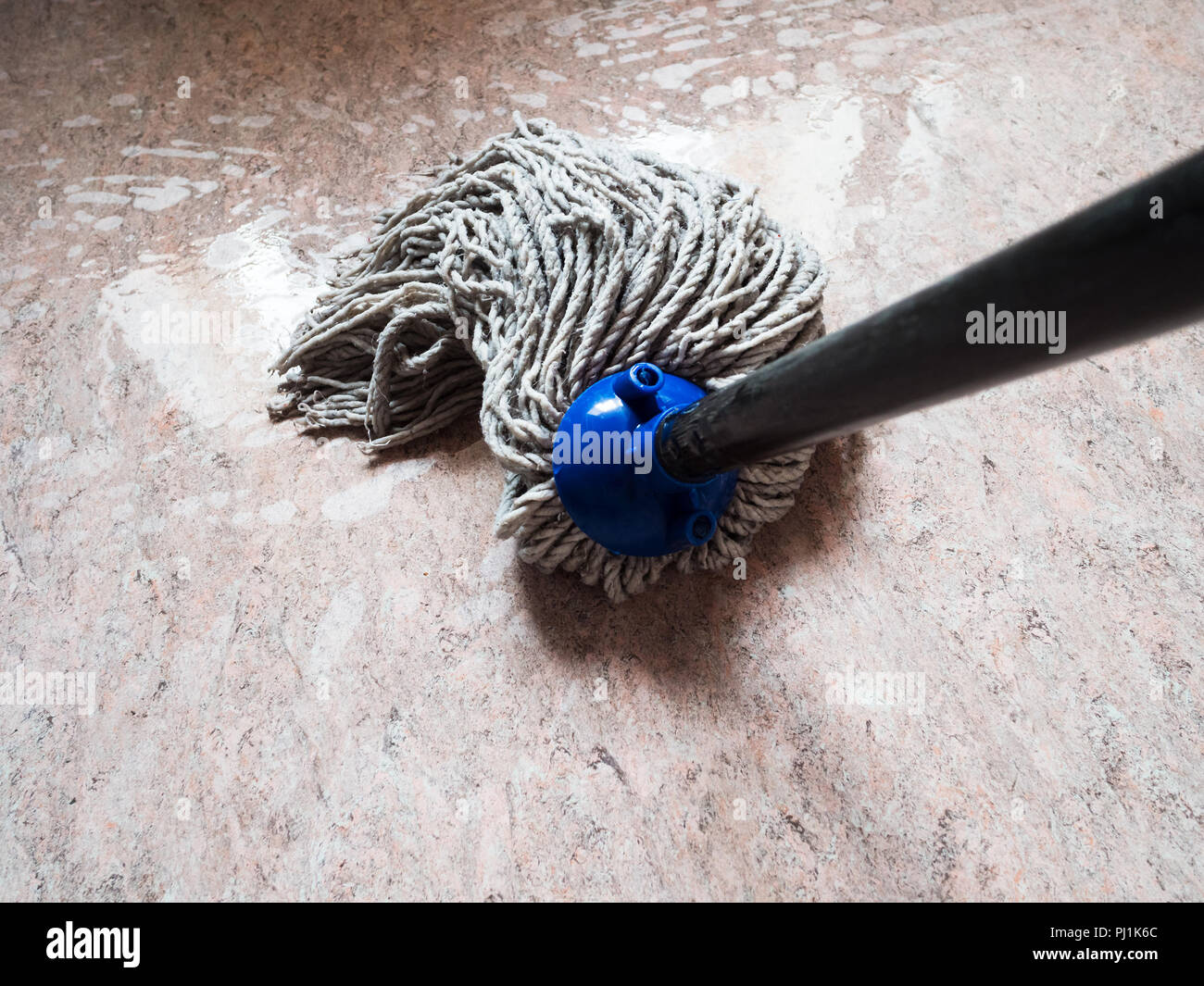 point-of-view shot of mopping floor by rope mop - Stock Image