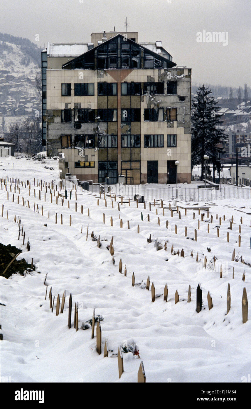 4th March 1993 A badly damaged building stands below ranks of snow-covered Bosnian Muslim graves in the Lion Cemetery in Sarajevo. The graves are all dated 1992. - Stock Image