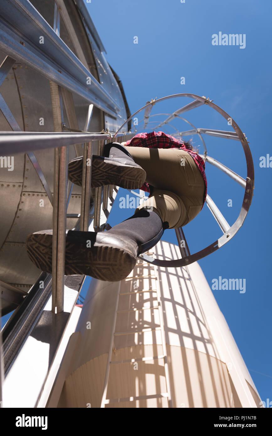 Female worker climbing bio gas plant Stock Photo