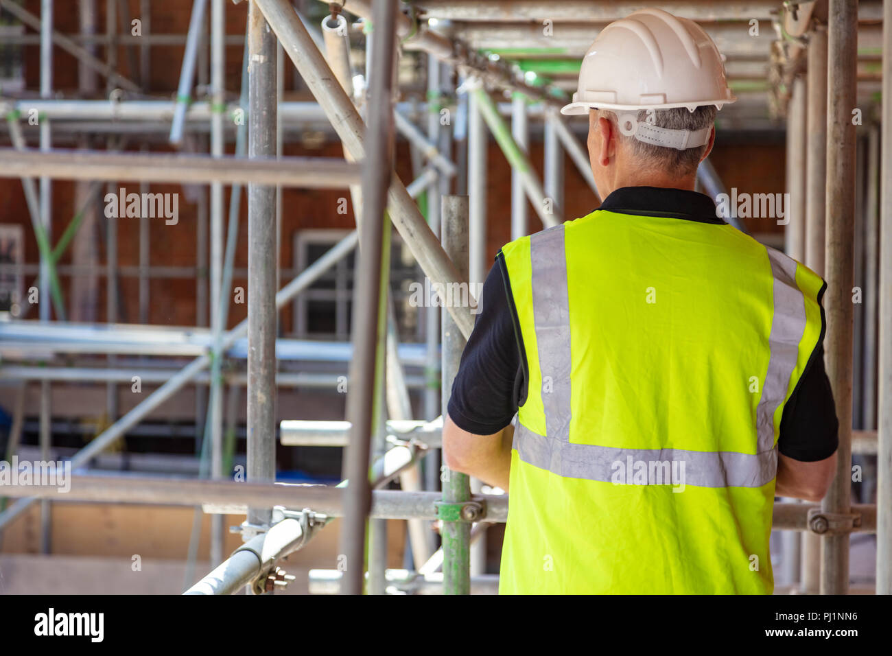 Rear view of male builder construction worker on building site wearing hard hat and hi vis vest - Stock Image