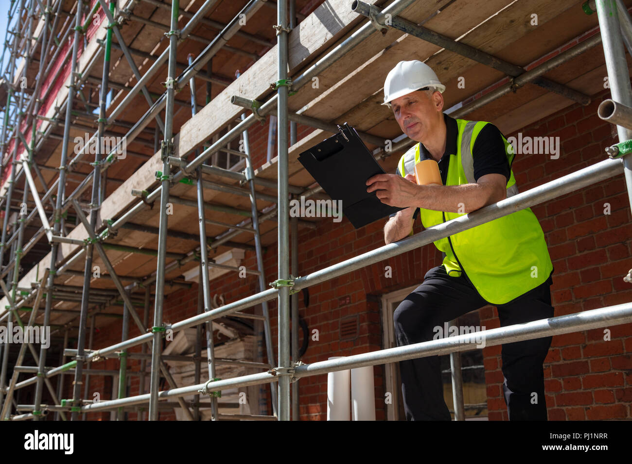 Male builder foreman, construction worker or architect on site holding a clipboard and drinking a mug of coffee or tea - Stock Image