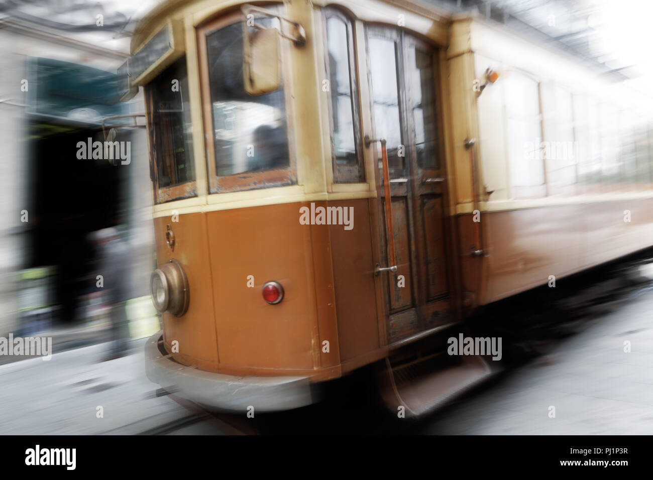 Old city blurred background with vintage yellow tramway - Stock Image