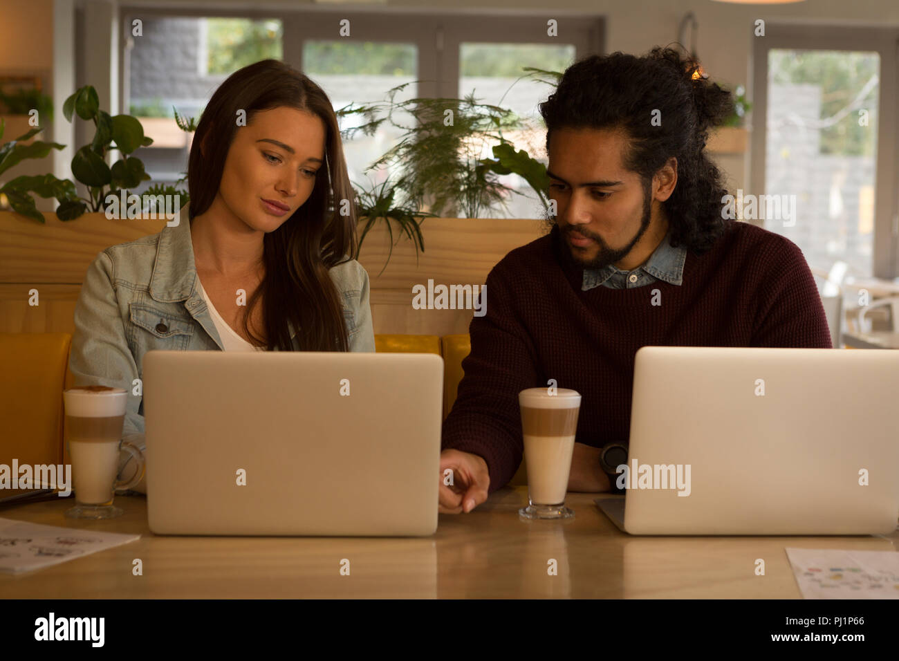 Couple discussing over laptop in cafe - Stock Image