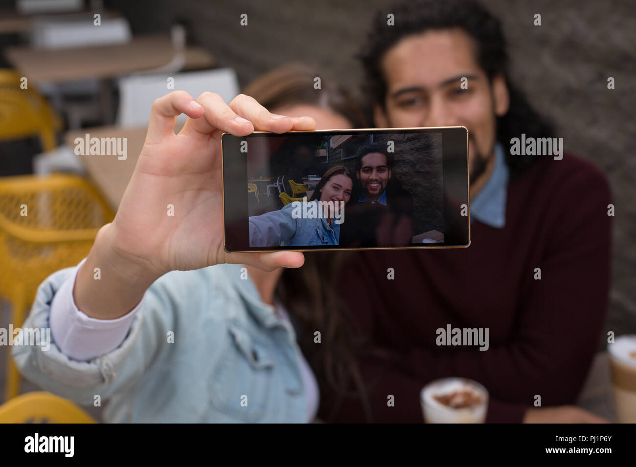 Couple taking selfie at outdoor cafe Stock Photo