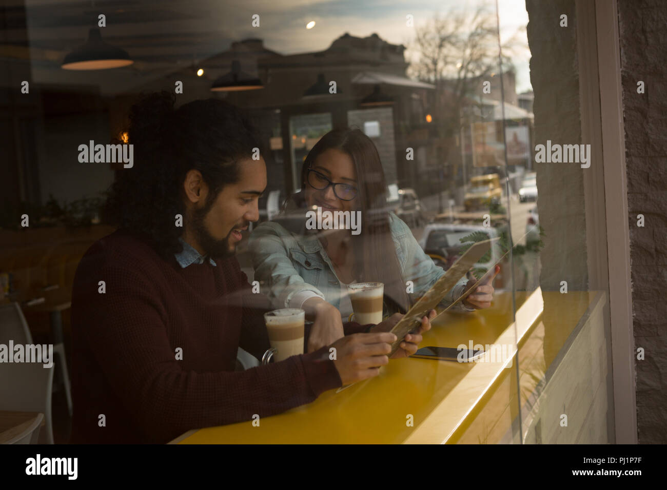 Couple discussing menu card in cafe - Stock Image