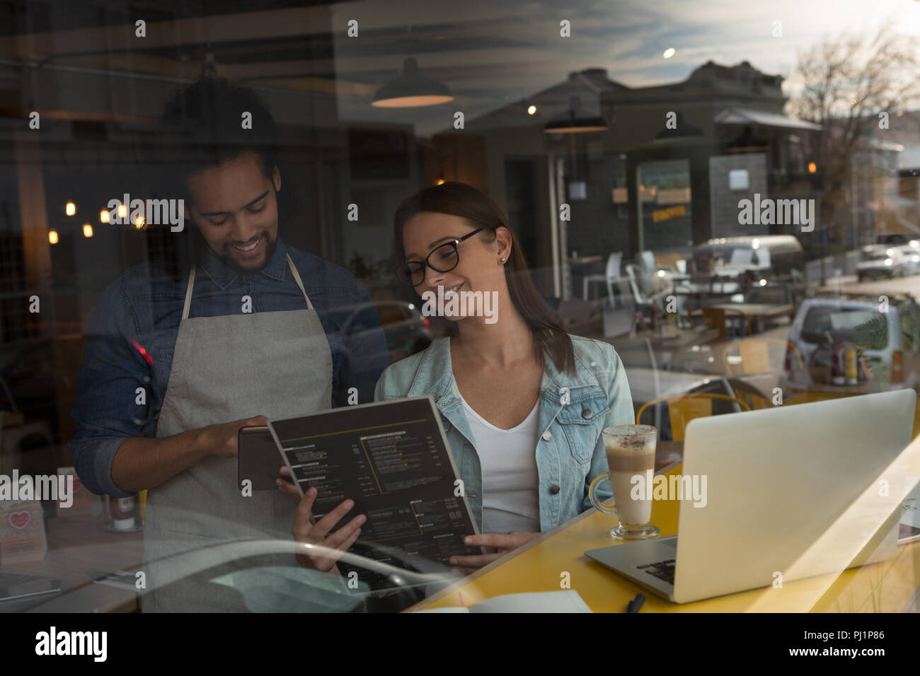 Woman discussing menu card with waiter - Stock Image