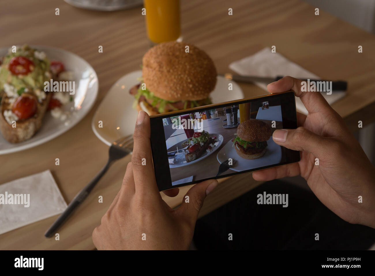 Woman taking photo of food in cafe - Stock Image