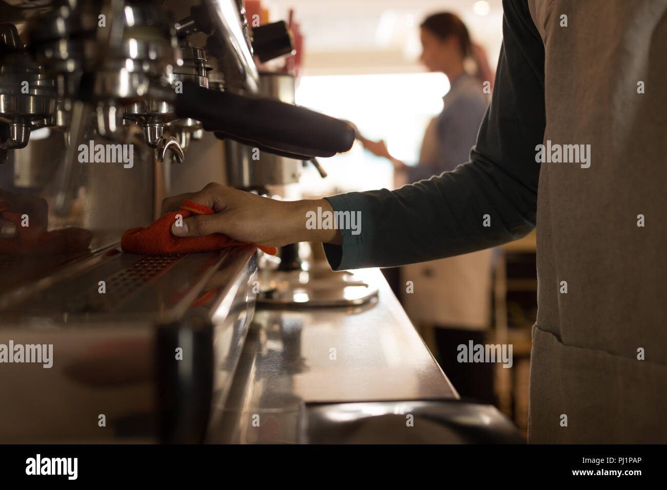 Waiter cleaning coffee machine at coffee counter - Stock Image