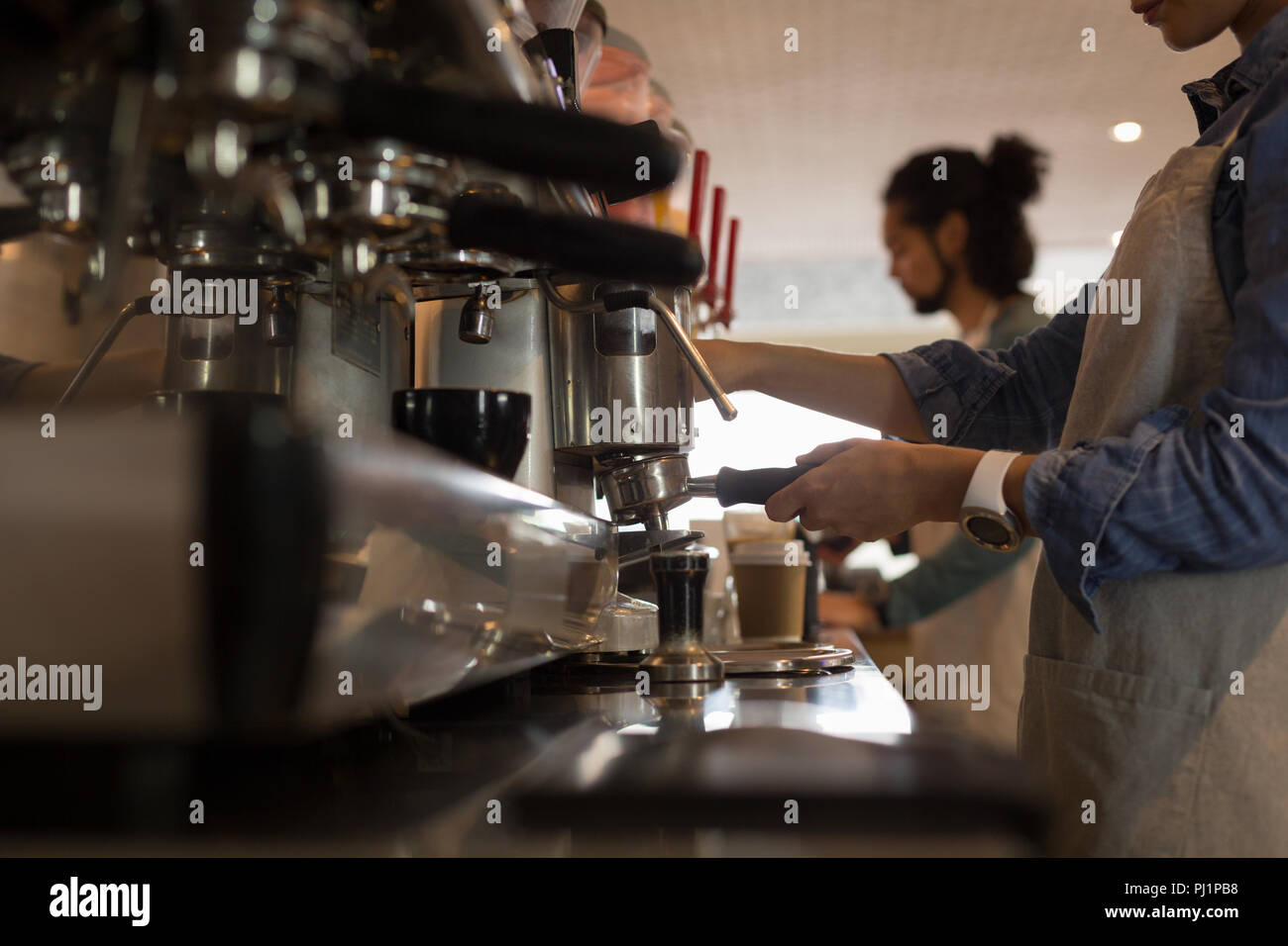 Waitress preparing coffee at coffee machine in cafe - Stock Image