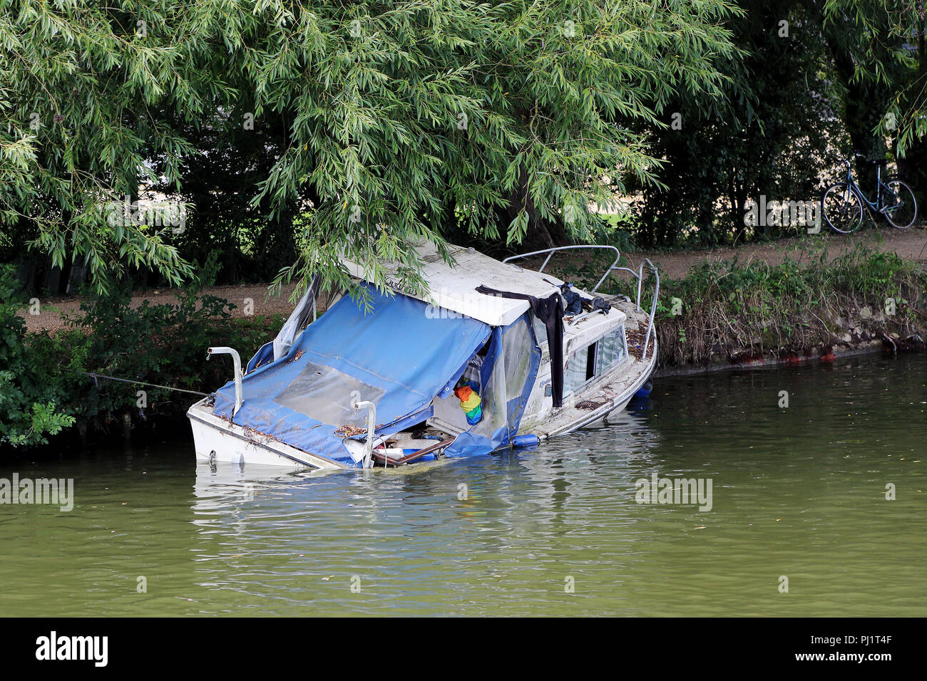 A small cabin cruiser boat appears to be sinking on the