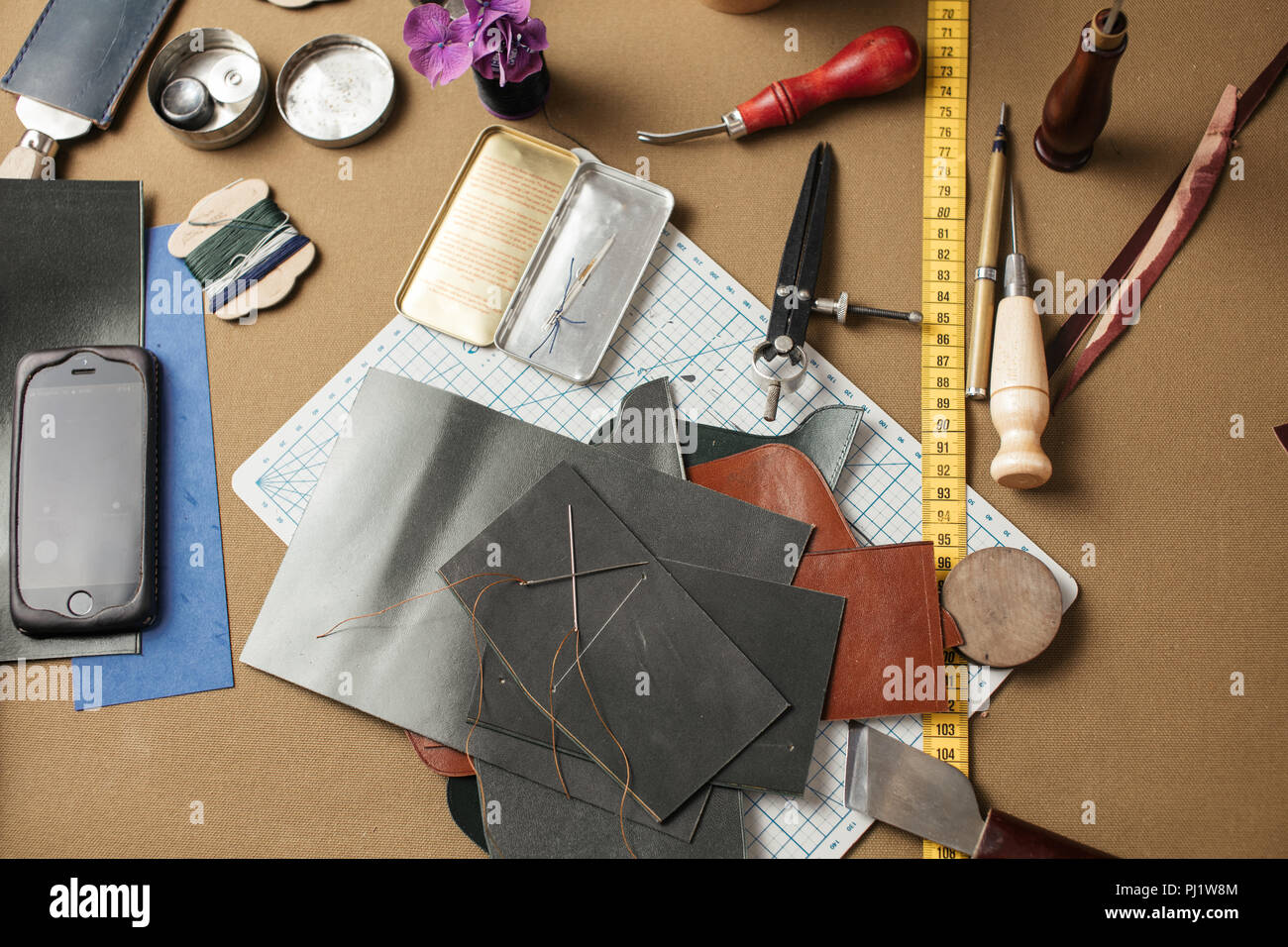 Set of leather craft tools on paper background. Workplace for shoemaker. - Stock Image