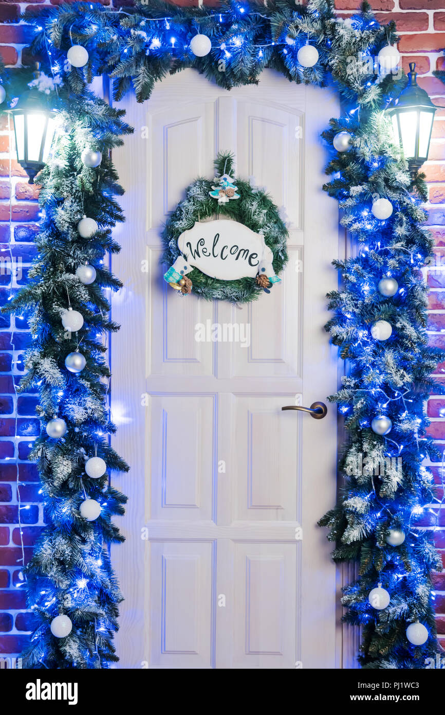 Door with an inscription welcom, two lanterns and garlands of pine branches - Stock Image