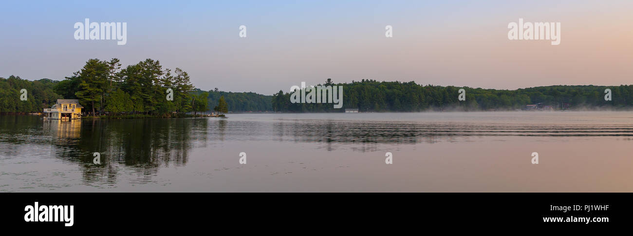 A small lakeside cottage on an Island in the Muskokas, Ontario, at sunrise. - Stock Image