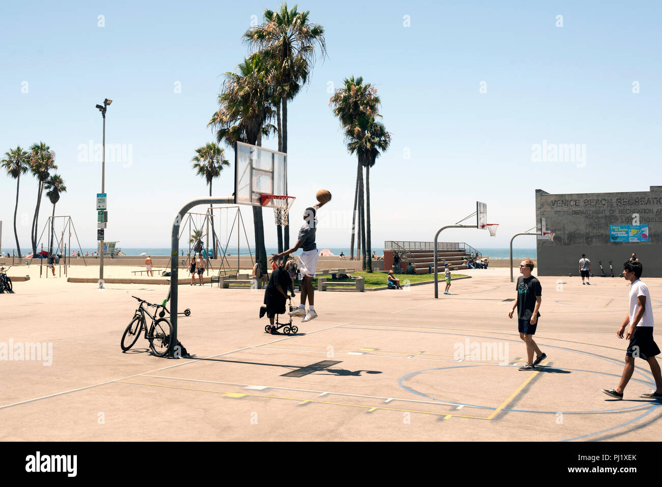 A black guy dunking in the basketball court outdoors in Venice beach, California in summer time - Stock Image