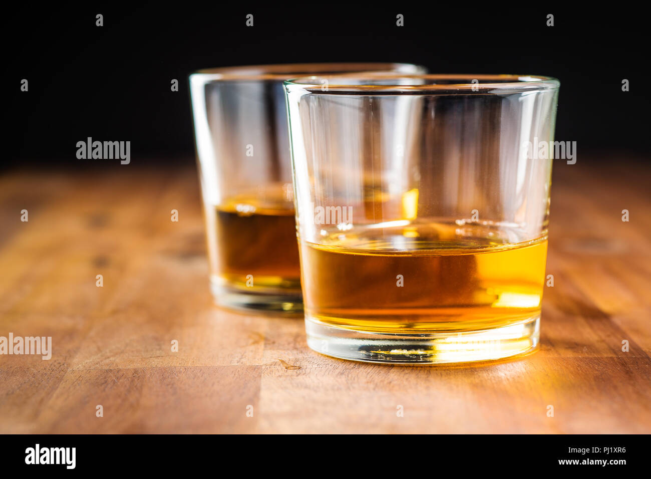 Glass of alcoholic drink wooden table. Whiskey in glass. - Stock Image