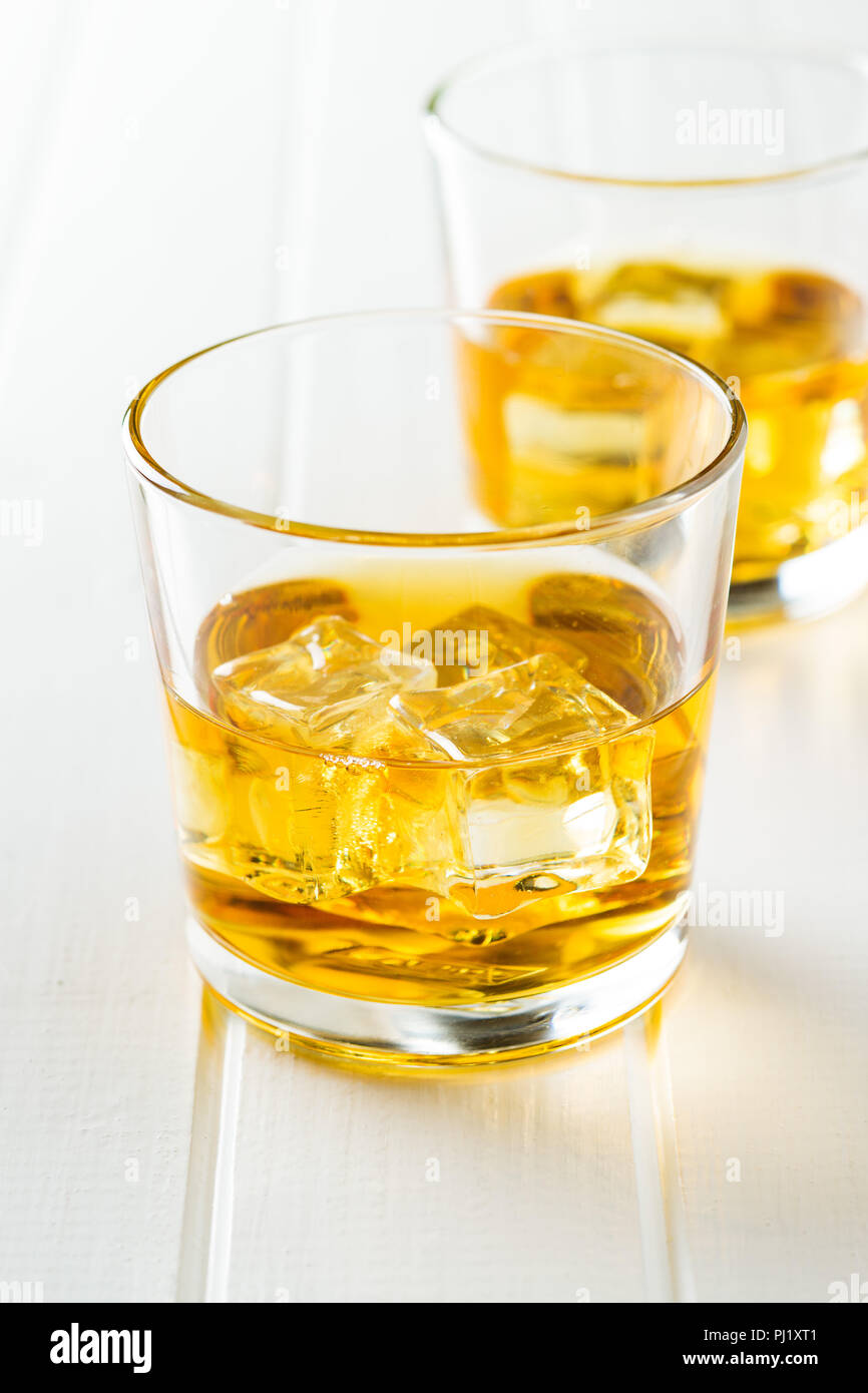 Glass of alcoholic drink with ice cubes on white table. Whiskey in glass. Stock Photo