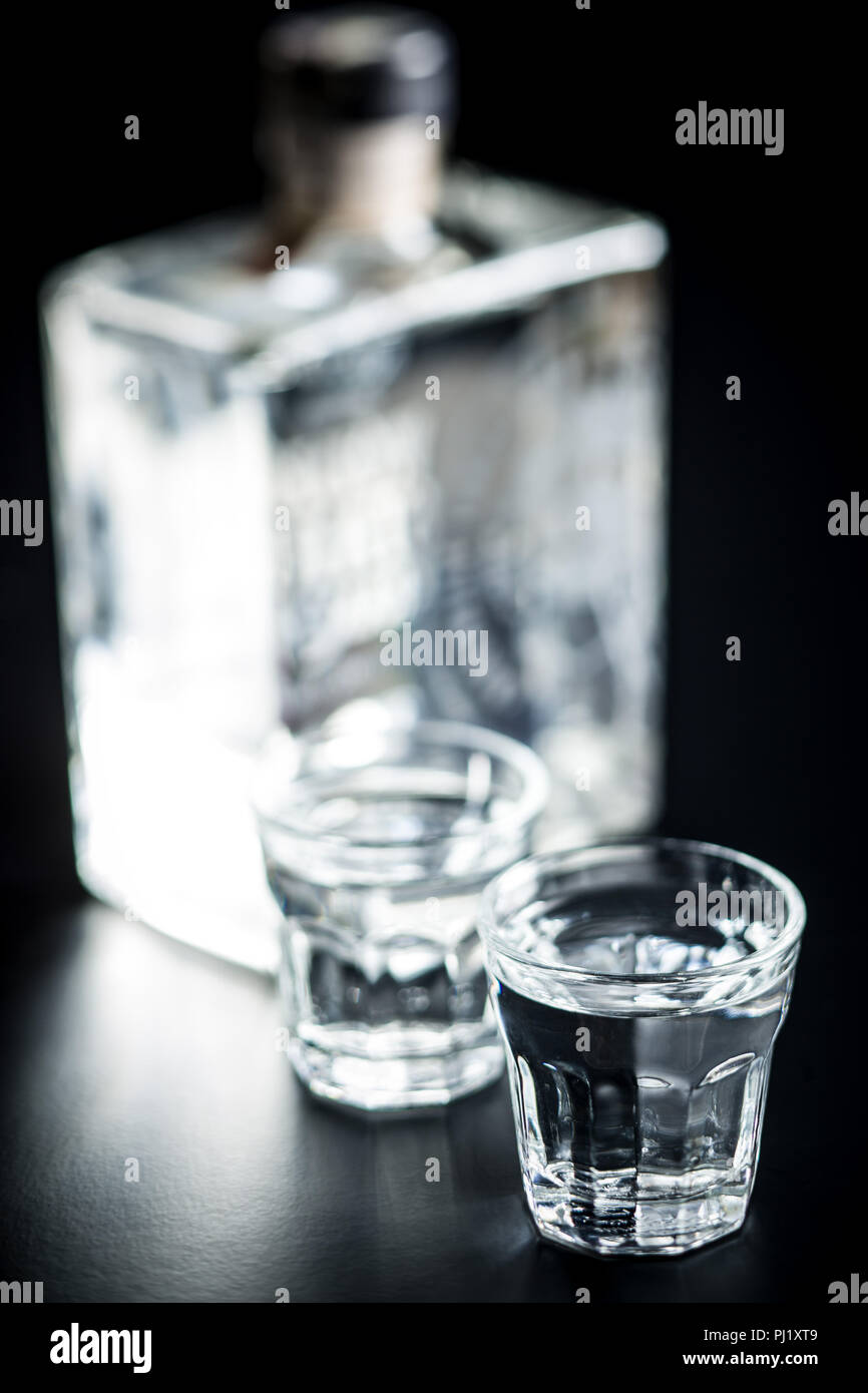 Vodka in shot glass. Transparent alcohol on black table. Stock Photo