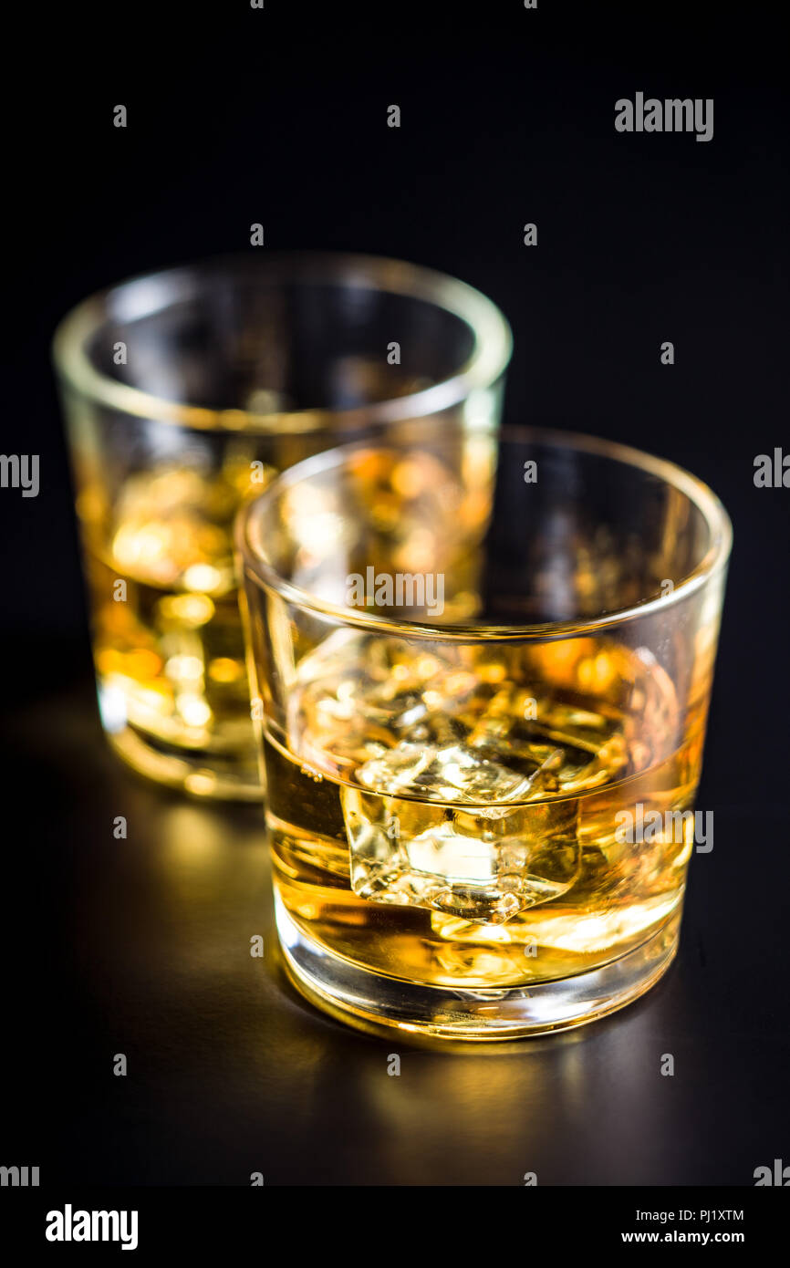 Glass of alcoholic drink with ice cubes on black table. Whiskey in glass. - Stock Image