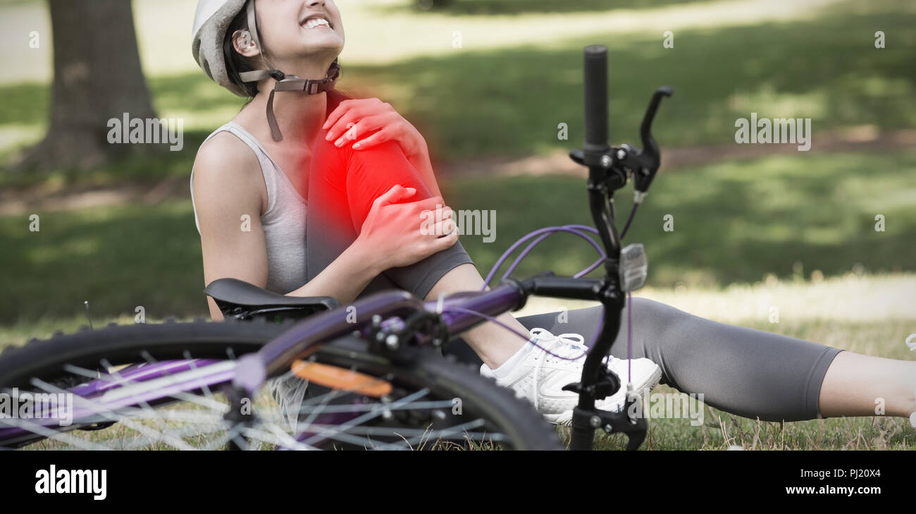 Composite image of female bicyclist with hurt leg sitting in park - Stock Image