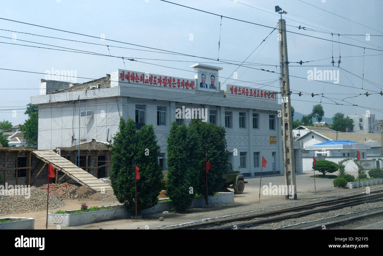 Railway station large building with the portraits of Kim Il Sung and Kim Jong Il on it. - Stock Image