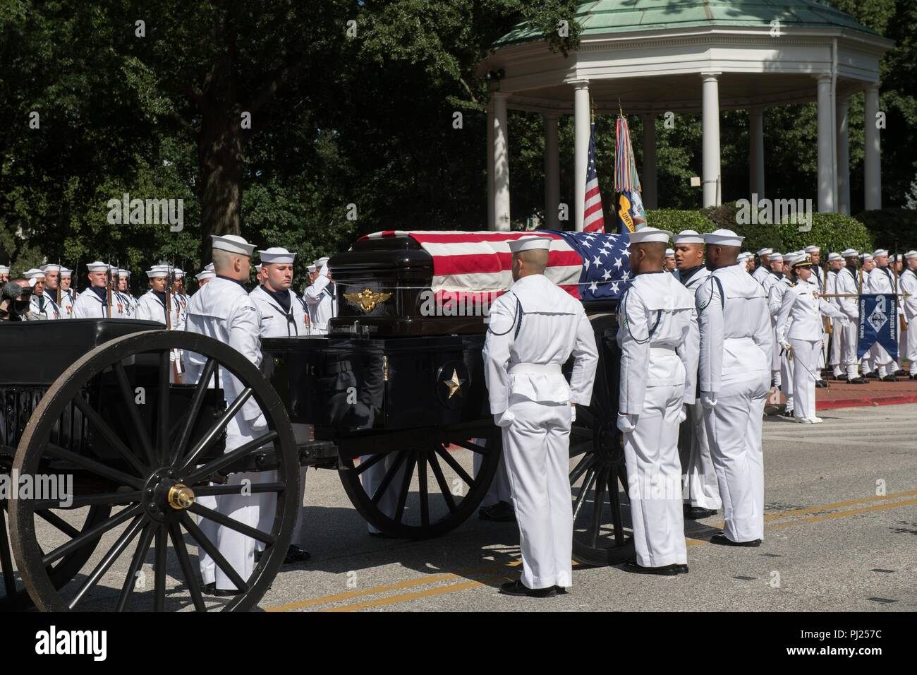 The flag draped casket of Sen. John McCain on a horse-drawn caisson as Midshipmen prepare to move the casket to the final resting place a the United States Naval Academy Cemetery September 2, 2018 in Annapolis, Maryland. John S. McCain, III graduated from the United States Naval Academy in 1958. He was a pilot in the United States Navy, a prisoner of war in Vietnam, a Congressmen and Senator and twice presidential candidate. He received numerous awards, including the Silver Star, Legion of Merit, Purple Heart, and Distinguished Flying Cross. - Stock Image