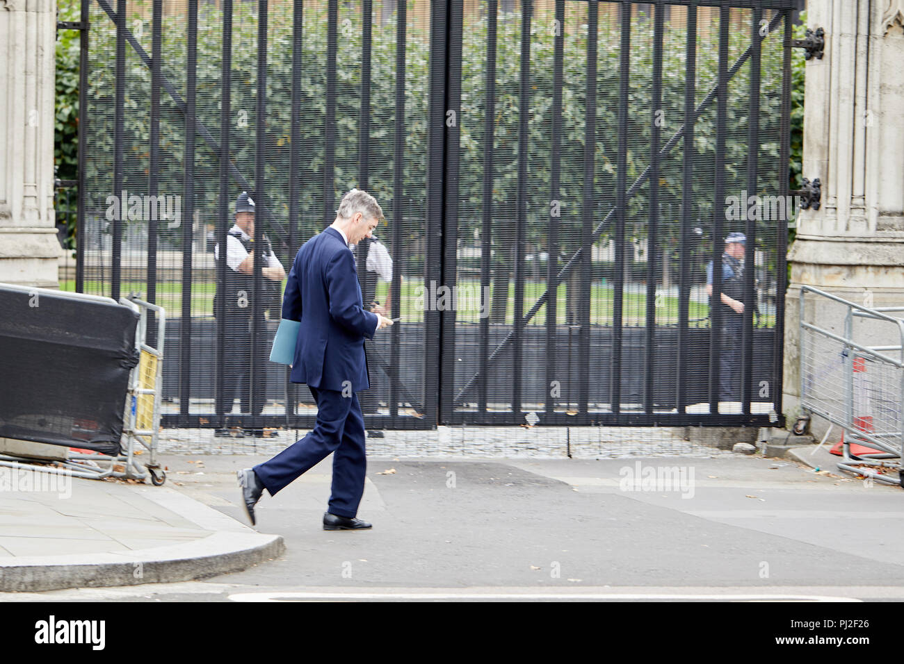 London, UK. 4th September 2018. British Conservative party politician and Member of Parliament Jacob Rees-Mogg on his phone passing the Houses of Parliament today. Credit: Kevin Frost/Alamy Live News - Stock Image