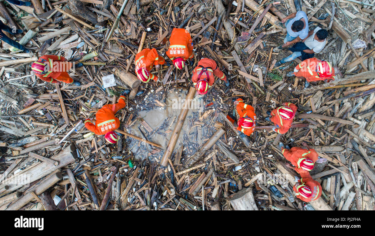 Malipo. 4th Sep, 2018. Aerial photo taken on Sept. 4, 2018 shows rescuers searching for survivors after a mudflow at flood-hit Mengdong Township in Malipo County of Zhuang and Miao Autonomous Prefecture of Wenshan, southwest China's Yunnan Province. Heavy rainstorms that started pounding Mengdong Township on Sunday have triggered a flood and mudslide, which left five people dead and seven others injured. Credit: Hu Chao/Xinhua/Alamy Live News - Stock Image