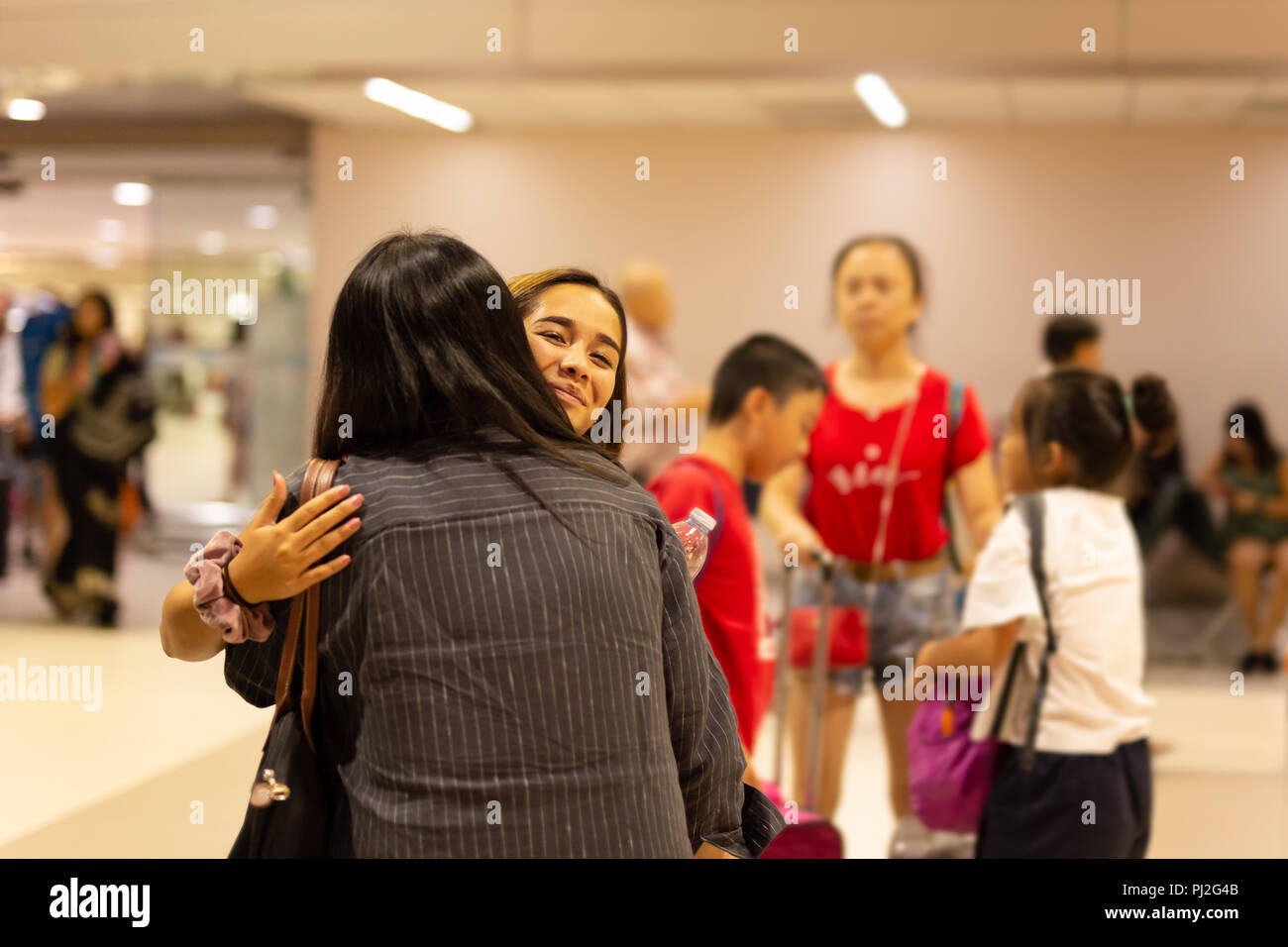 Happy daughter hugging mother on arrival at the airport - Stock Image