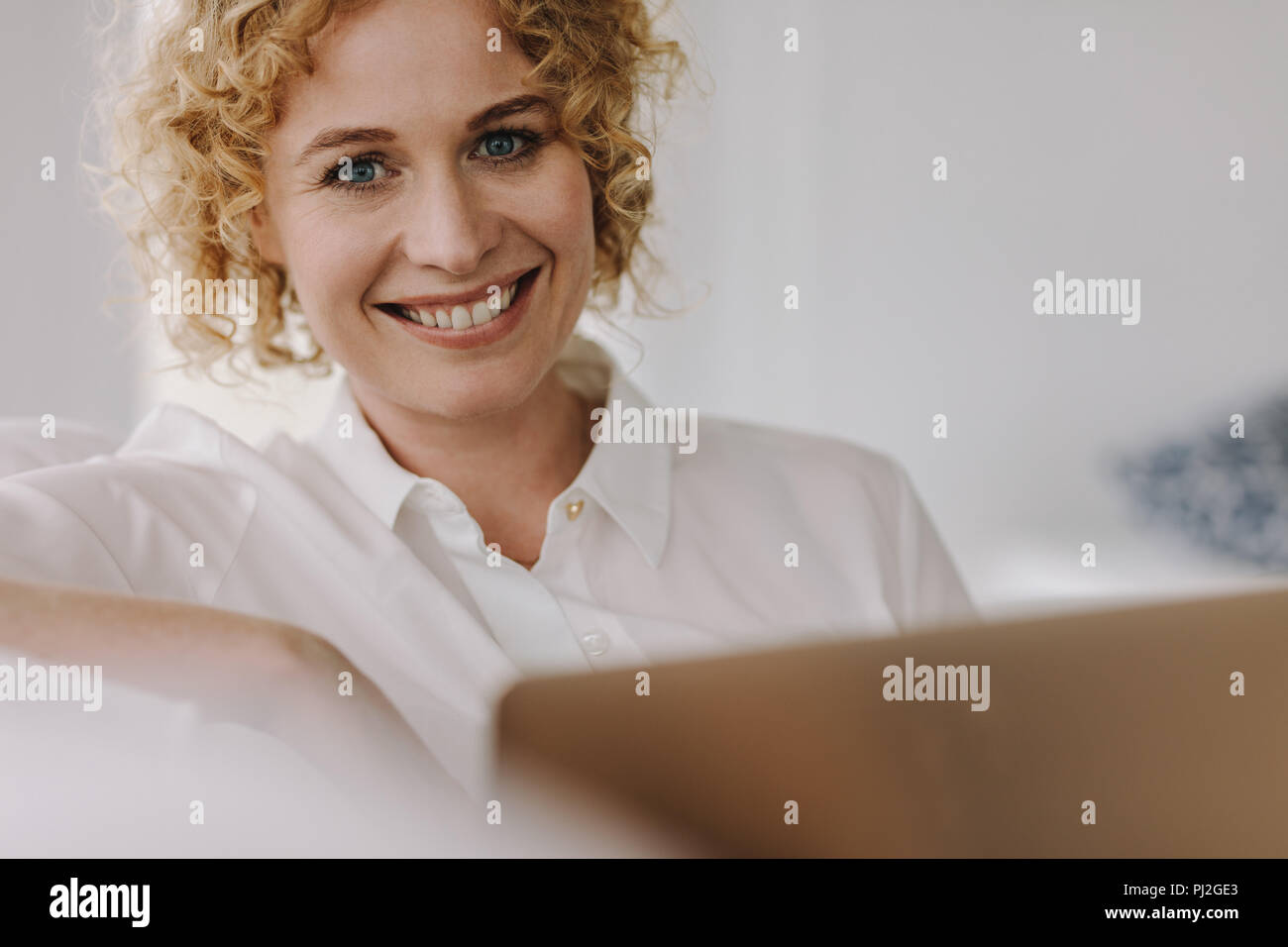 Portrait of a smiling businesswoman working on a laptop. Brown curly haired woman sitting at home working on laptop. - Stock Image