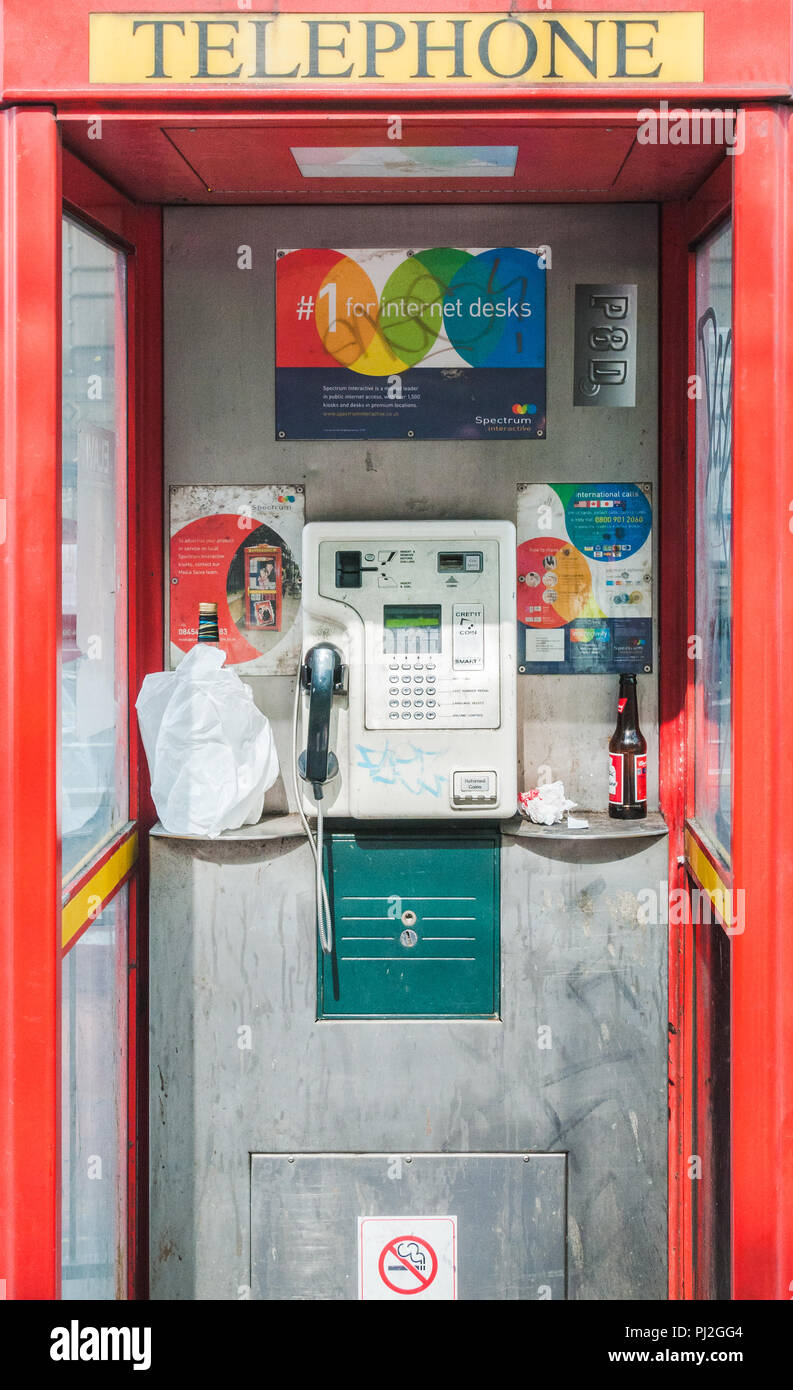 Derelict red telephone box in Manchester with graffiti and empty bottles of alcohol - Stock Image