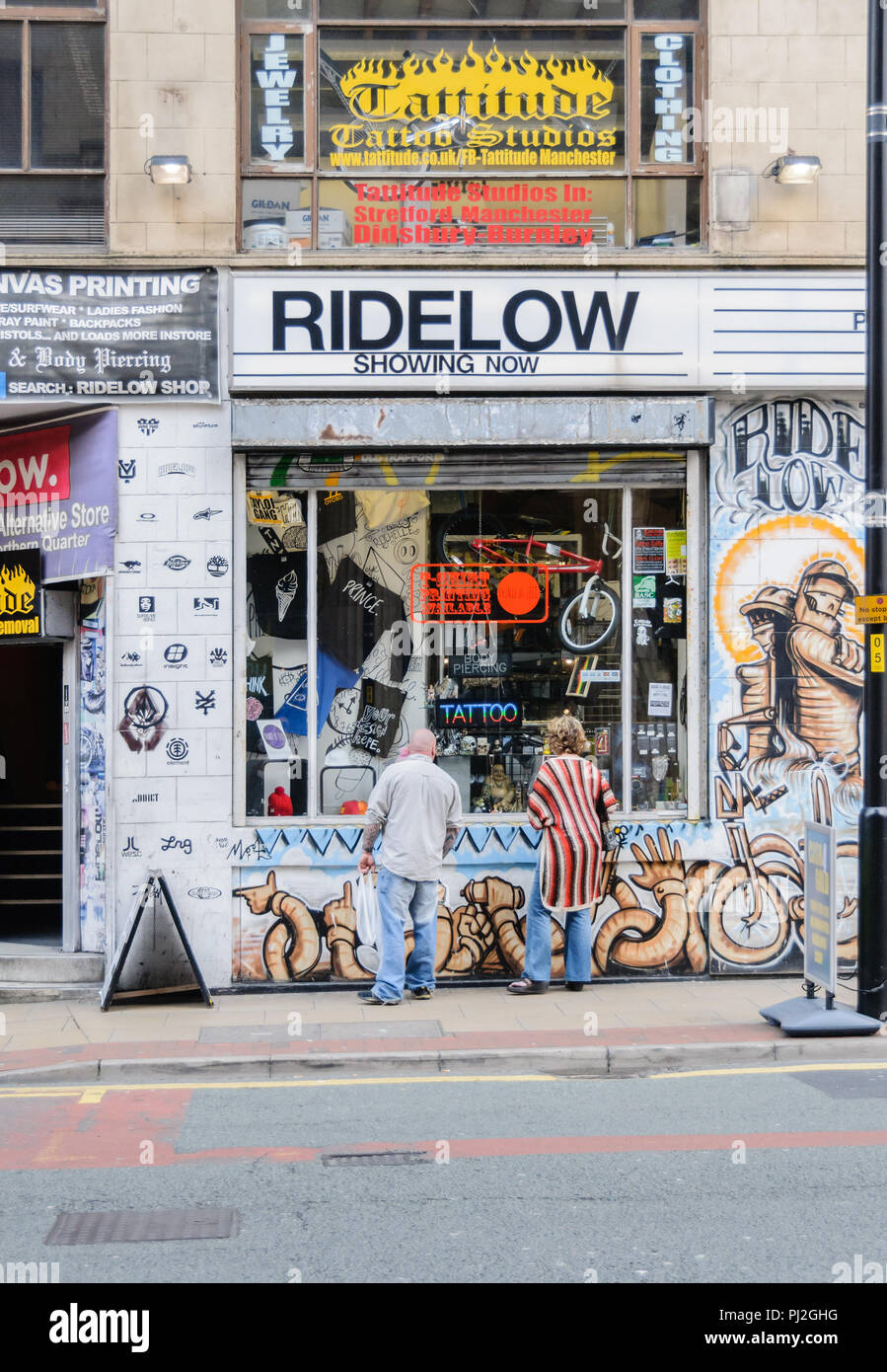 Couple looking in bicycle shop window in Northern Quarter in Manchester - Stock Image