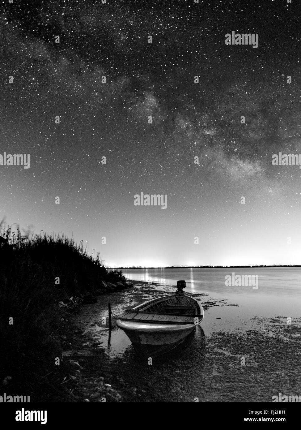 night landscape photography. lake boat and milky way - Stock Image