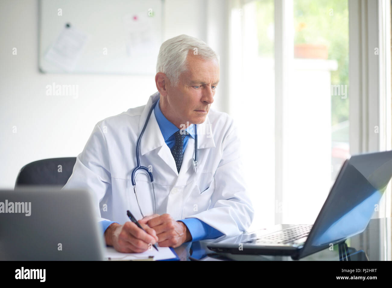 Portrait of male doctor writing down the diagnosis while sitting at consulting room. - Stock Image
