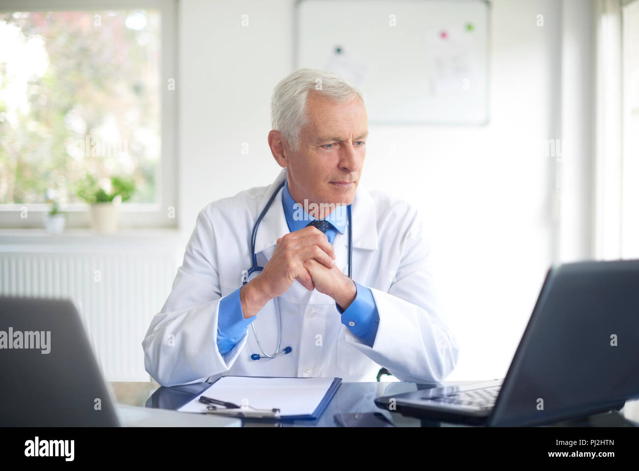 Portrait of senior male doctor working on laptop while sitting in consulting room. - Stock Image