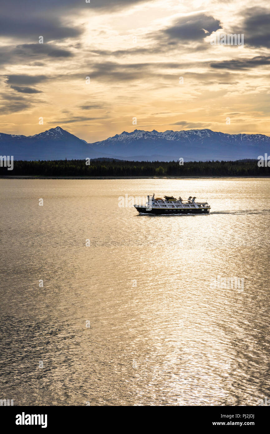 The National Geographic tour ship 'Sea Lion' at dawn in the entrance to Glacier Bay, Alaska, USA - Viewed from a cruise ship sailing the Inside Passag - Stock Image