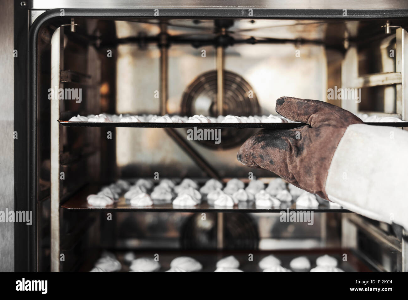 Close up of cook putting meringue cookies in the oven. - Stock Image
