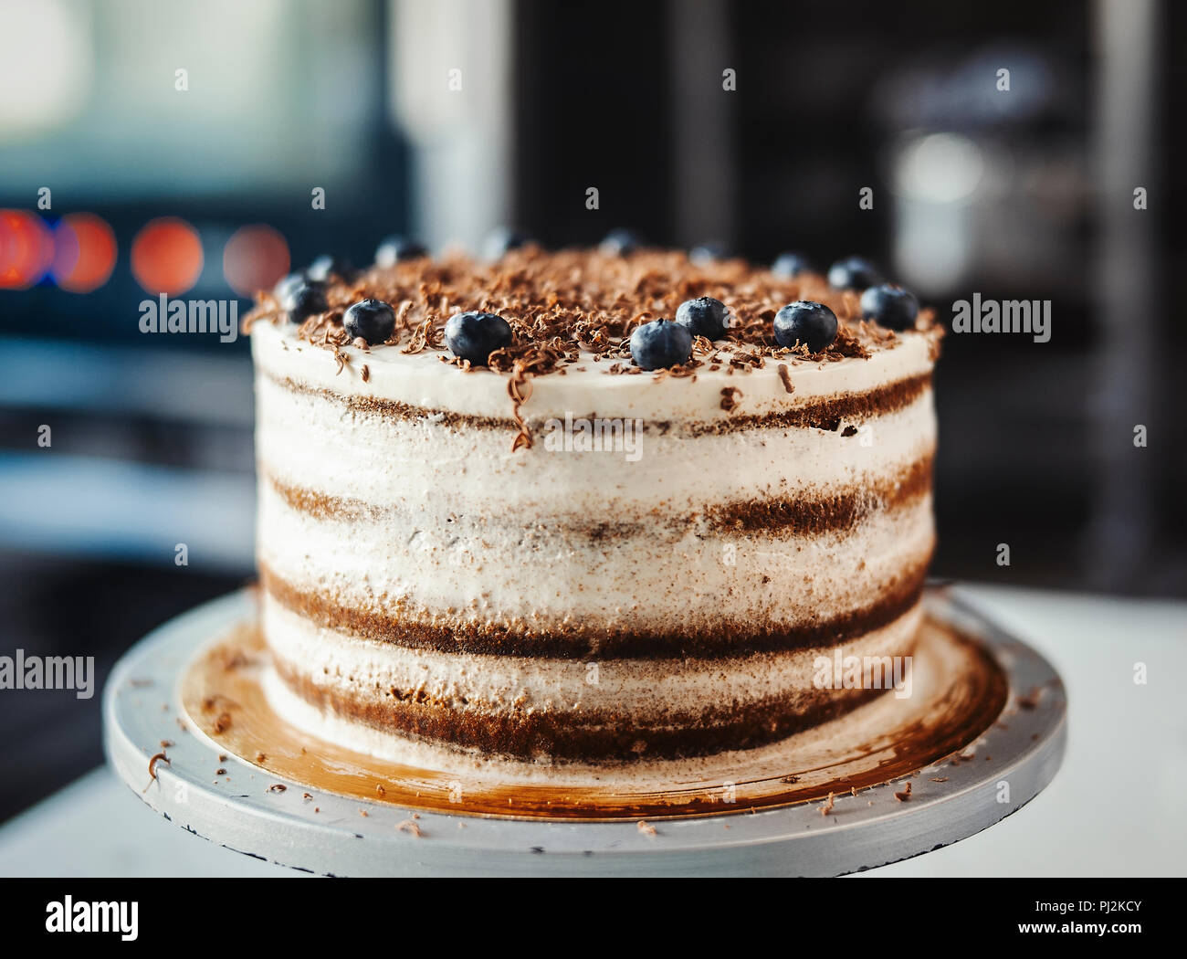Close up of chocolate cake with cream cheese and berries. - Stock Image