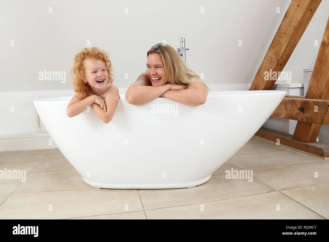 Mother and Daughter looking over the edge of a freestanding Bath Tub in a modern Bathroom - Stock Image