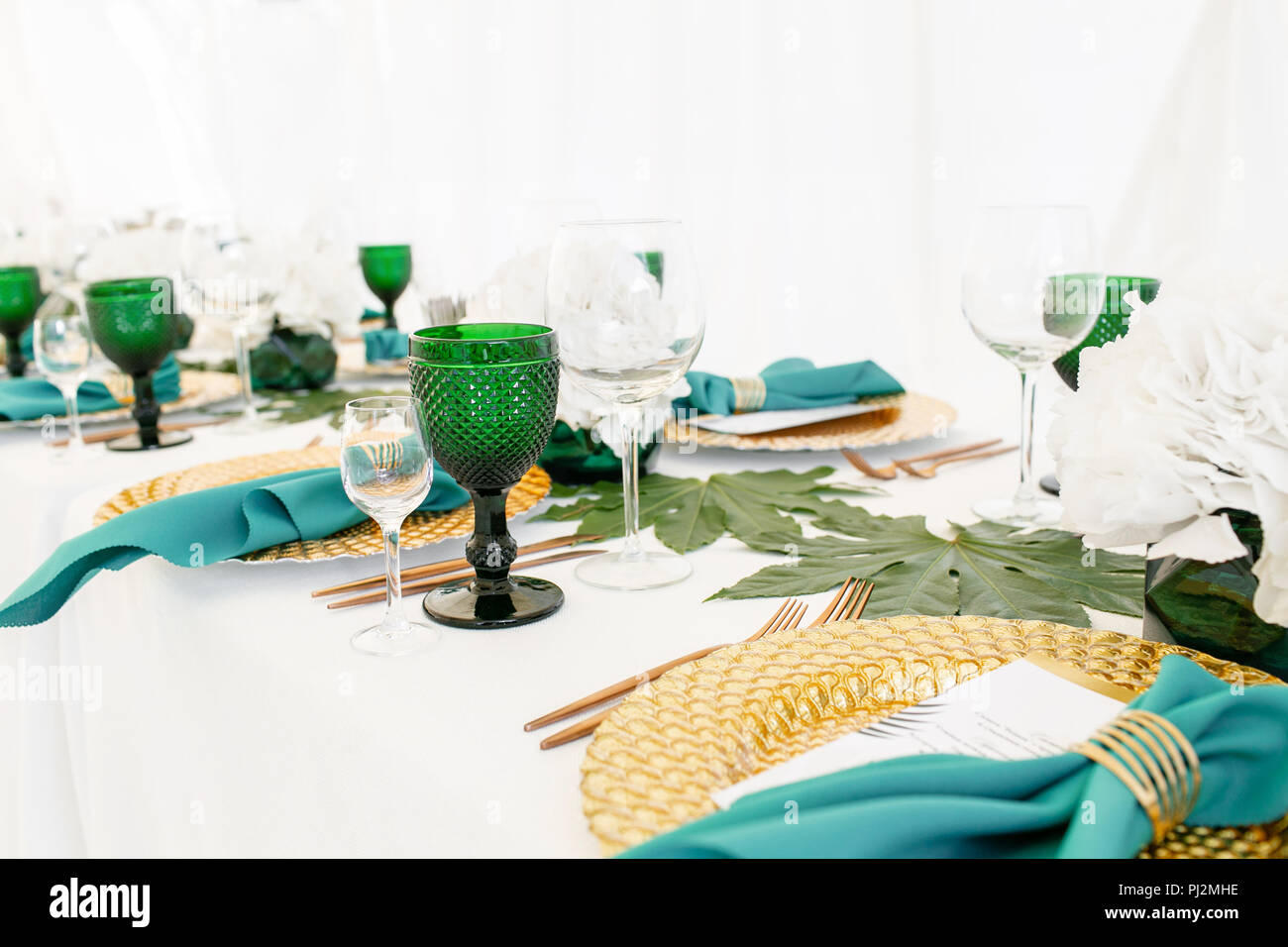 Interior of tent for wedding diner, ready for guests. Served round banquet table outdoor in marquee decorated hydrangea flowers, Golden dishes and green napkins. Catering concept - Stock Image