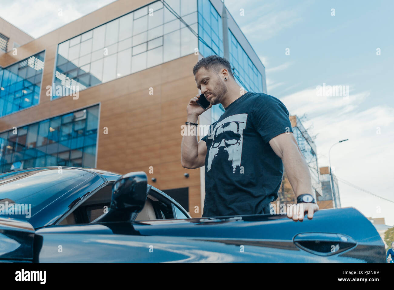 Close up of attractive man getting out of the car and talking by mobile phone. - Stock Image