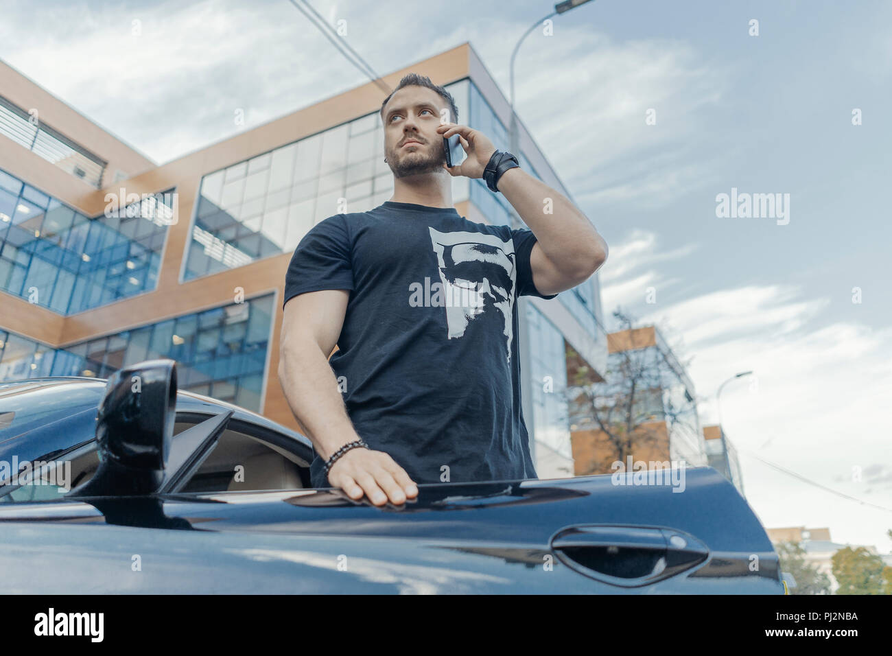 Close up of man getting out of the black car and talking by mobile phone. - Stock Image