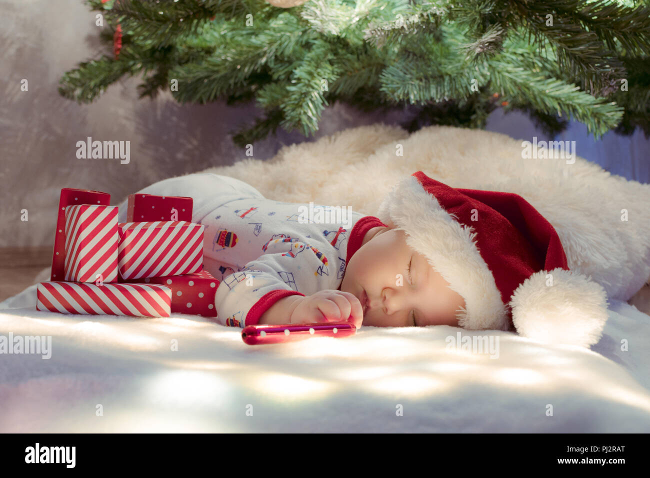 Cute newborn baby sleeping under Christmas tree near red gifts wearing Santa Claus hat. - Stock Image