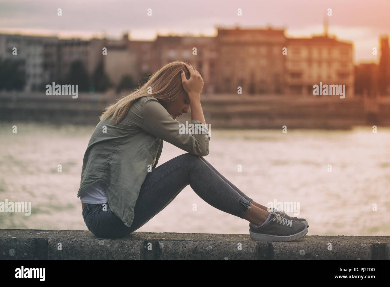 Sad woman sitting at the riverbank. - Stock Image
