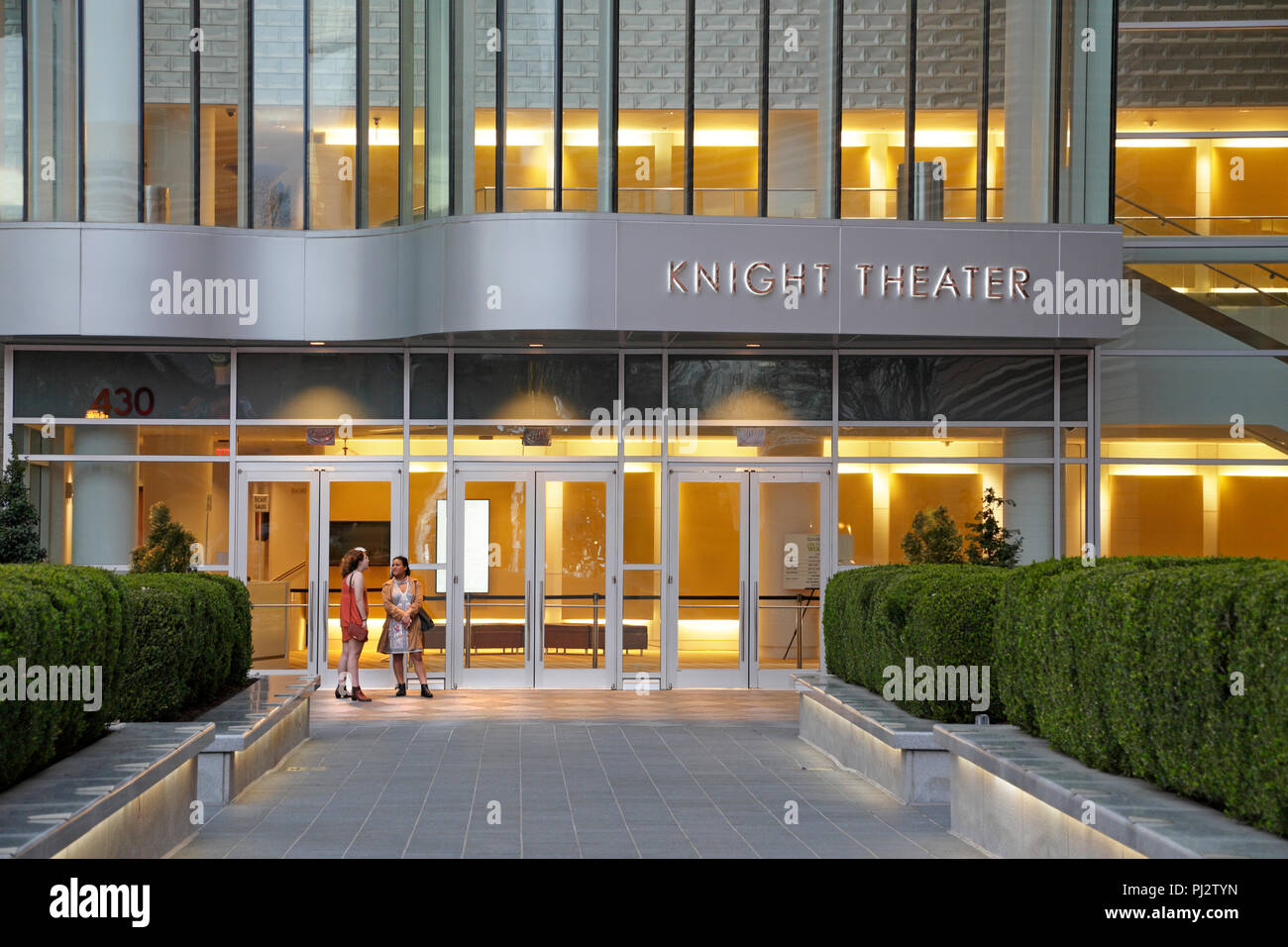 Charlotte, North Carolina. Two women outside Knight Theater in downtown at dusk. Stock Photo
